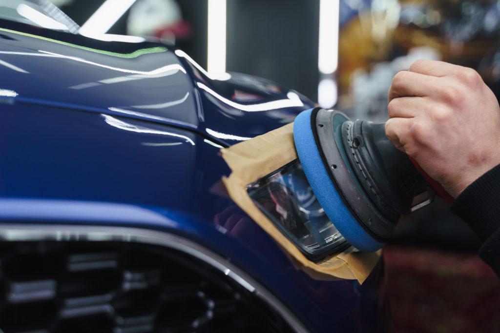 Man prepares car headlights for polishing