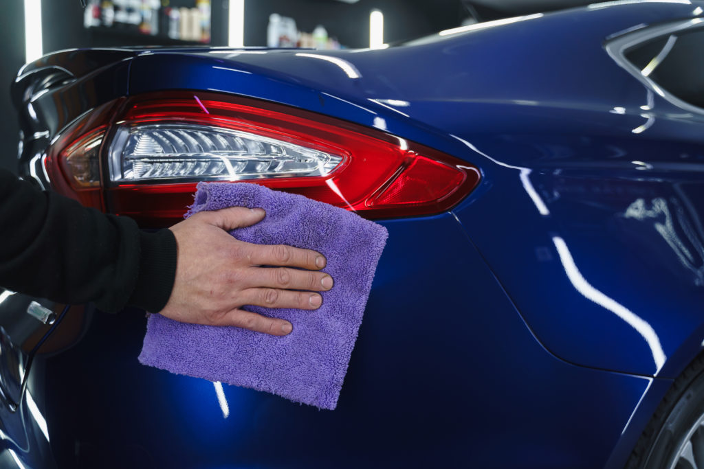 Man polishes a car in garage